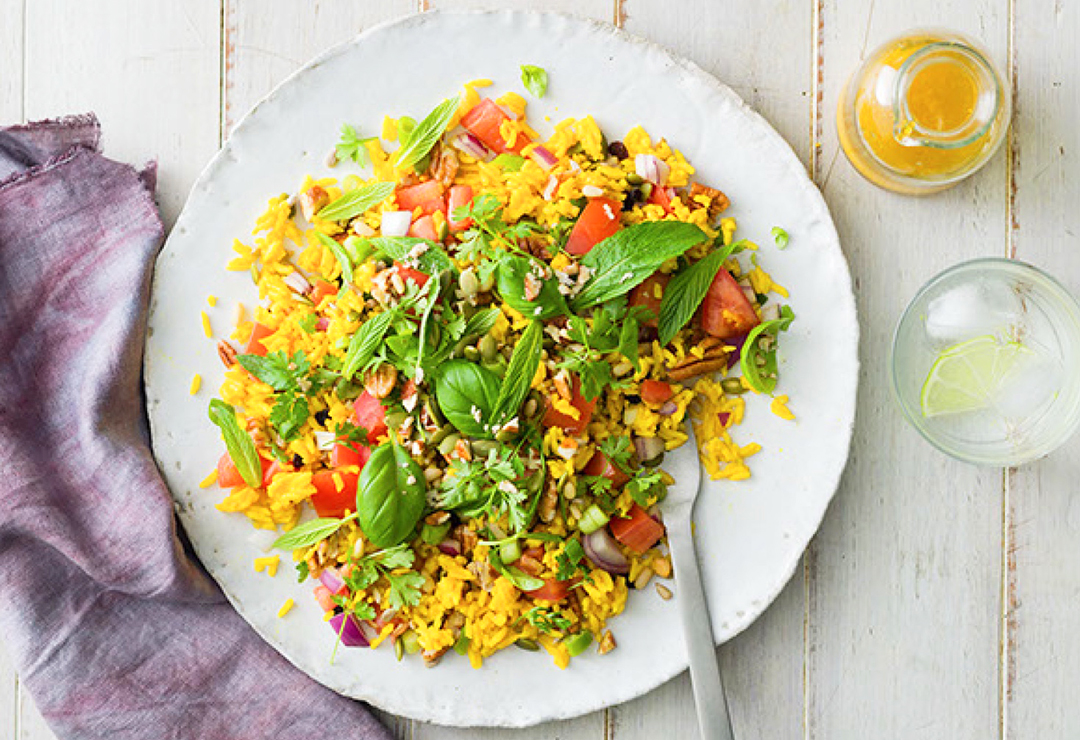 Yellow rice salad with seeds, nuts and green herbs